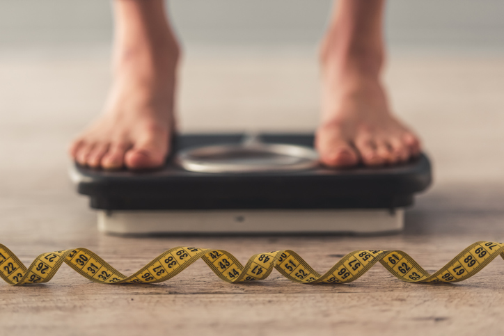 体重計に乗って現実を直視する(写真:iStock)